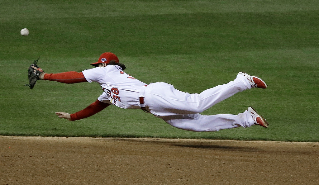 . St. Louis Cardinals\' Pete Kozma can\'t catch a ball hit by Los Angeles Dodgers\' Juan Uribe during the sixth inning of Game 1 of the National League baseball championship series, Friday, Oct. 11, 2013, in St. Louis. (AP Photo/Charlie Neibergall)