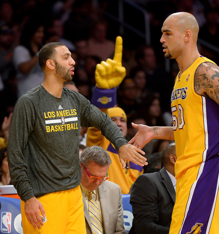 . Newly acquired Laker Kendall Marshall, left, welcomes center Robert Sacre back to the bench during a substitution, Friday, December 20, 2013, at Staples Center. (Photo by Michael Owen Baker/L.A. Daily News)