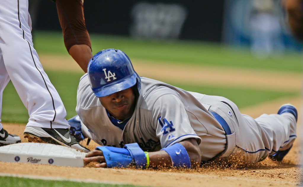 . Los Angeles Dodgers\' Yasiel Puig is picked off first base in the fourth inning against the San Diego Padres in a baseball game in San Diego, Sunday, June 23, 2013. (AP Photo/Lenny Ignelzi)