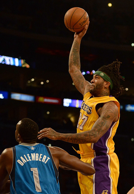 . Los Angeles Lakers forward Jordan Hill (27) shoots over Dallas Mavericks center Samuel Dalembert (1) in the first quarter during an NBA basketball game in Los Angeles, Calif., on Friday, April 4, 2014.  (Keith Birmingham Pasadena Star-News)