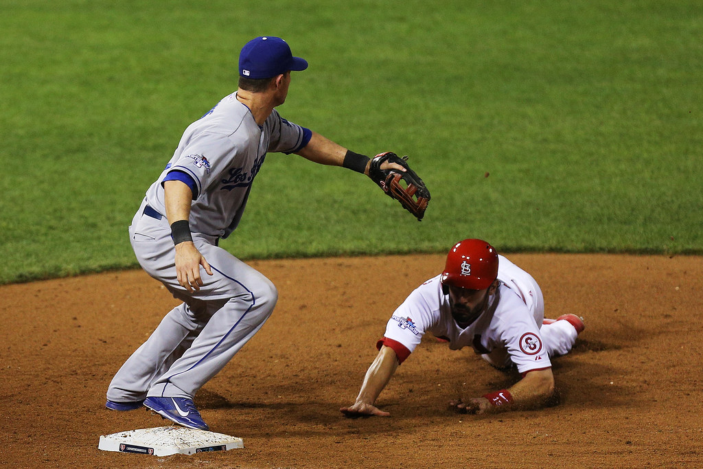 . ST LOUIS, MO - OCTOBER 11:  Matt Carpenter #13 of the St. Louis Cardinals dives back to first base against Michael Young #10 of the Los Angeles Dodgers in the 11th inning during Game One of the National League Championship Series at Busch Stadium on October 11, 2013 in St Louis, Missouri.  (Photo by Ed Zurga/Getty Images)
