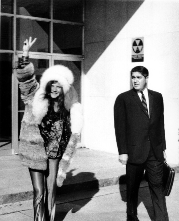 . Rock singer Janis Joplin, 26, shows a victory sign as she leaves police headquarters with her attorney, Herbert Goldburg, in Tampa, Fla., on Nov. 20, 1969.  Joplin had a preliminary hearing on obscenity charges lodged against her when she allegedly cursed a police who interupted a performance.  (AP Photo)