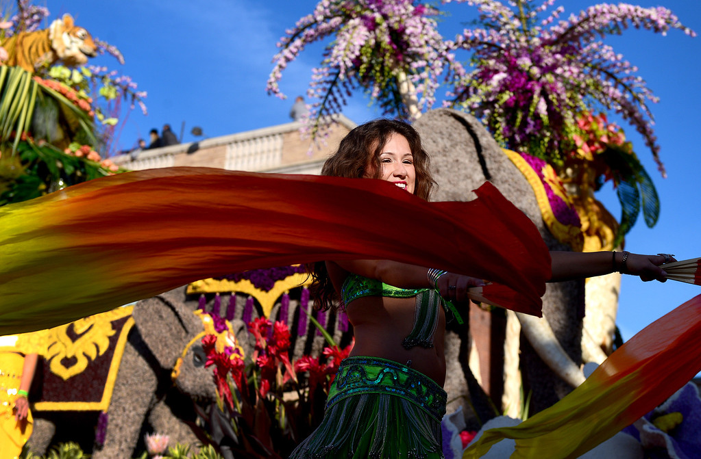 """. A woman dances alongside Dole\'s \""""Sunrise at the Oasis\"""" float as it heads down Colorado Boulevard during the 125th Rose Parade in Pasadena, CA January 1, 2014. (Photo by Sarah Reingewirtz/Pasadena Star-News)"""