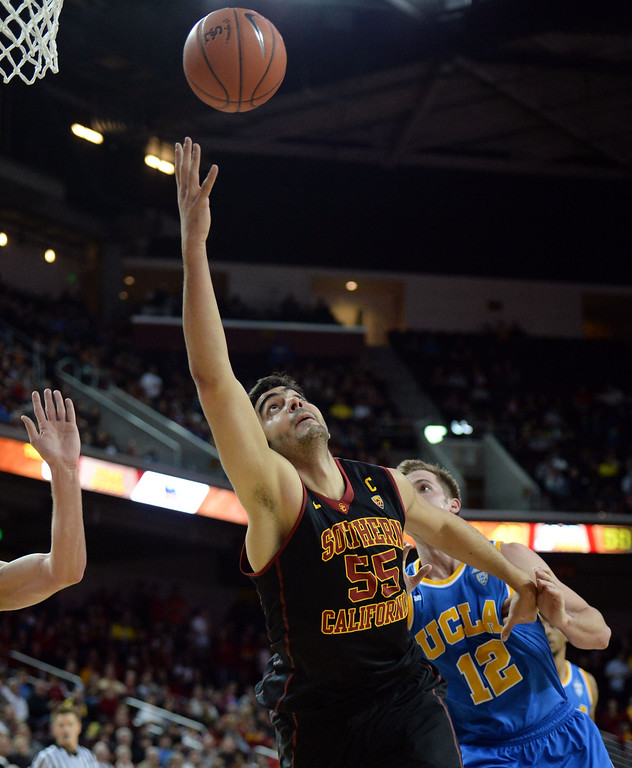 . Southern California\' Omar Oraby (55) reaches for a loose ball past UCLA\'s David Wear (12) in the second half of a PAC-12 NCAA basketball game at Galen Center in Los Angeles, Calif., on Saturday, Feb. 8, 2014. UCLA won 83-73. (Keith Birmingham Pasadena Star-News)