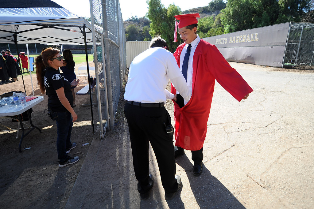 . Students are checked for phones, noise makers prior to the Whittier High School graduation at Whittier College in Whittier, Calif., on Wednesday, June 4, 2014.  (Keith Birmingham/Pasadena Star-News)
