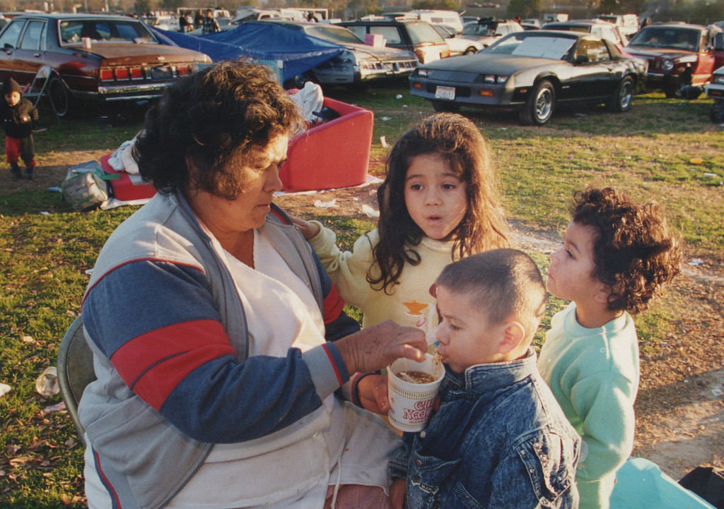 . Children are fed a cup of noodles from a woman at a family camp site in North Hollywood Park, in North Hollywood, CA. 1/17/1994, photo by (John McCoy/Los Angeles Daily News)