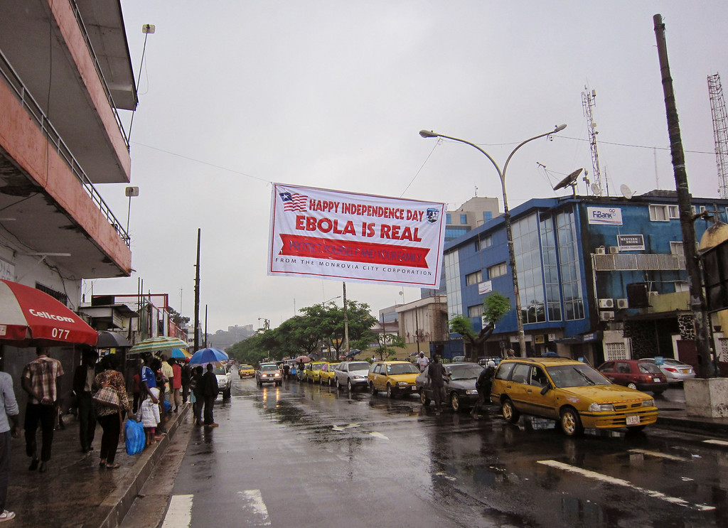 . In this photo taken on Monday, July 28, 2014, people hang out in a street under a  banner which warns people to be cautious about Ebola, in Monrovia, Liberia. Two American aid workers in Liberia have tested positive for the virus and are being treated there. U.S. health officials said Monday that the risk of the deadly germ spreading to the United States is remote. (AP Photo/Jonathan Paye-Layleh)