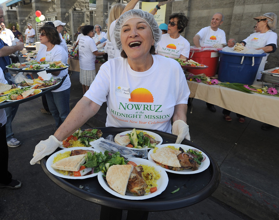 . Firouzeh Ameri gets ready to serve meals. The Midnight Mission is celebrating its 100th anniversary this year. As part of the yearlong festivities, the Persian community is helping the Midnight Mission celebrate by sharing Persian New Year or Nowruz. Volunteers at the event served a traditional Persian meal to the homeless in the middle of 6th Street and San Pedro. Los Angeles, CA. March 14, 2014 (Photo by John McCoy / Los Angeles Daily News)