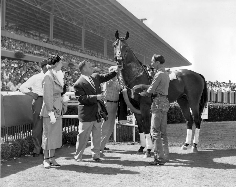 """. Citation is shown in the winner\'s circle after taking a bow at Hollywood Park in Inglewood, Ca., on July 21, 1951.  Citation, the first race horse to win $1 million, was retired to stud on July 20.  Standing with \""""Big Cy,\"""" from left, are, owner Lucille Parker Wright, trainer Jimmy Jones, holding bridle, and exercise boy Freeman McMillen.   (AP Photo)"""
