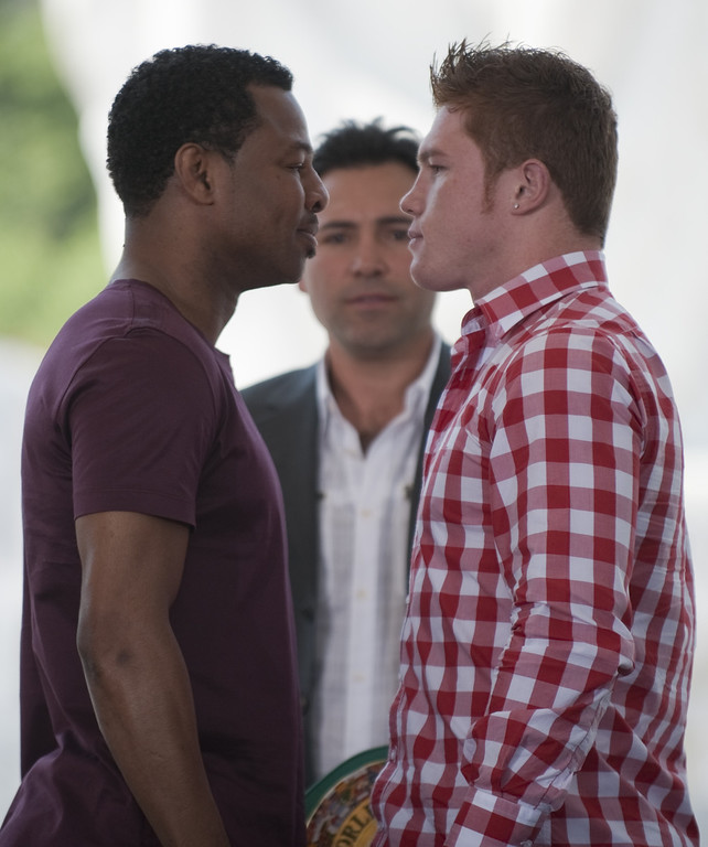 """. Mexican boxer Saul Alvarez (R) aka \""""Canelo\"""" and US boxer Sugar Shane Mosley face each other while US former boxer and promoter Oscar de la Hoya (C) looks on, after a press conference in Mexico city on March 08,2012. Mosley will face Alvarez on May 05.  (JOHAN ORDONEZ/AFP/Getty Images)"""