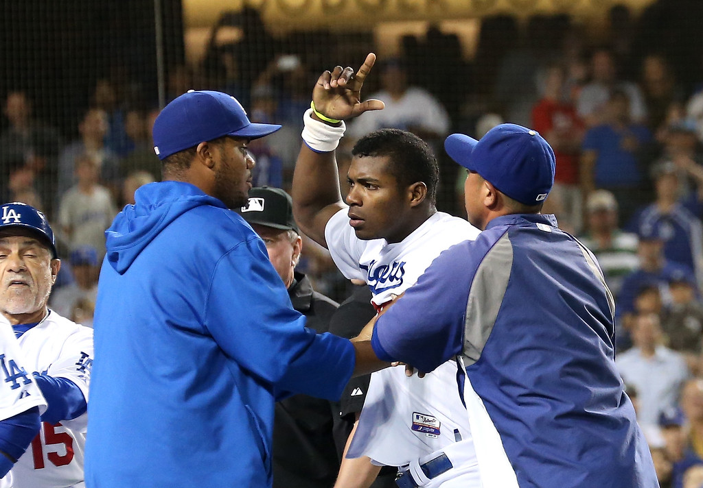. LOS ANGELES, CA - JUNE 11:  Yasiel Puig #66 of the Los Angeles Dodgers is restrained by teammates during a benches clearing brawl after Zack Greinke was hit by a pitch in the seventh inning against the Arizona Diamondbacks at Dodger Stadium on June 11, 2013 in Los Angeles, California.  Puig had been hit earlier in the game.  (Photo by Stephen Dunn/Getty Images)