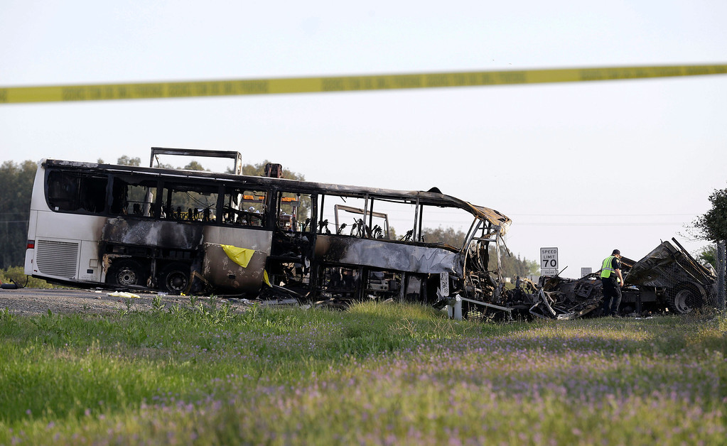 . A California Highway Patrol Officer looks over the demolished cab of FedEx truck that crashed into a tour bus, at left, on Interstate 5 Thursday in Orland, Calif., Friday, April 11, 2014. At least ten people were killed and dozens injured in the fiery crash between the truck and a bus carrying high school students on a visit to a Northern California College. (AP Photo/Jeff Chiu)