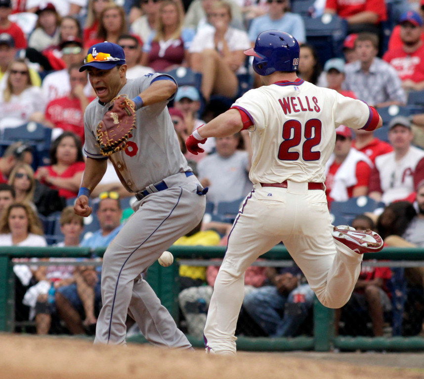 . Los Angeles Dodgers\' Jerry Hairston Jr., left, has trouble fielding a bad throw as Philadelphia Phillies\'  Casper Wells is safe at first in the ninth inning of a baseball game on Sunday, Aug. 18, 2013, in Philadelphia. The Phillies won 3-2. (AP Photo/H. Rumph Jr)