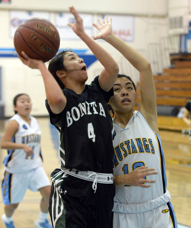 . Bonita\'s Ariana Abo (C) (4) drives to the basket past Walnut\'s Katya Echavez (10) in the first half of a prep basketball game at Walnut High School in Walnut, Calif., on Wednesday, Jan. 15, 2014. Bonita won 60-50. (Keith Birmingham Pasadena Star-News)