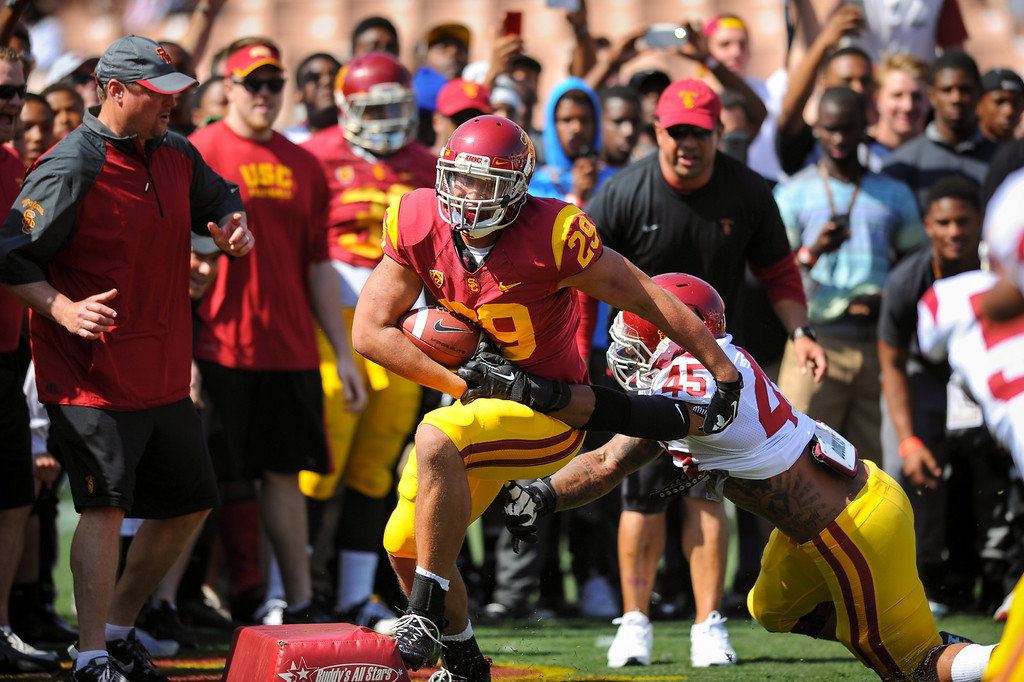 . USC RB Ty Isaac slips by LB Charles Burks during a drill before the spring game. (Photo by Michael Owen Baker/L.A. Daily News)