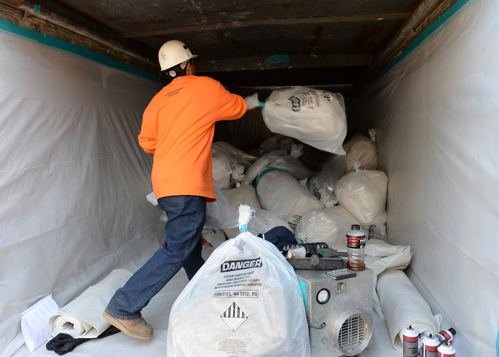 . A worker from Resource Environmental, Inc. throws in an Asbestos package that being removed from La Habra Heights City Hall on Wednesday January 22, 2014. More asbestos was found in the roofing material last week. (Staff Photo by Keith Durflinger/Pasadena Star-News)