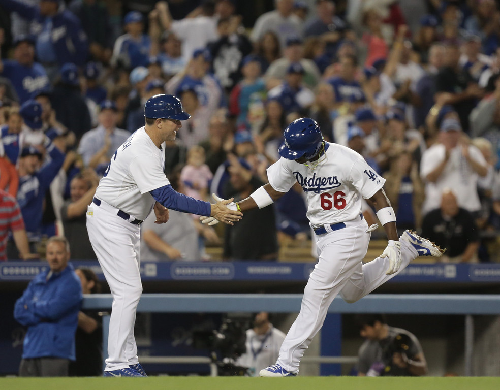 . Los Angeles Dodgers\' Yasiel Puig (66) celebrates with third base coach Tim Wallach as he rounds the bases after hitting a home run during the fifth inning of their baseball game against the San Diego Padres, Tuesday, June 4, 2013, in Los Angeles. Dodgers won 9-7. (AP Photo/Jason Redmond)