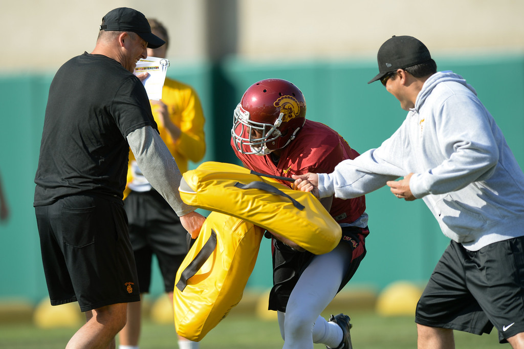 . USC WR Darreus Rogers is hit with pads by offensive coordinator Clay Helton, left, and tight ends coach Marques Tuiasosopo at practice, Thursday, March 27, 2014, at USC. (Photo by Michael Owen Baker/L.A. Daily News)