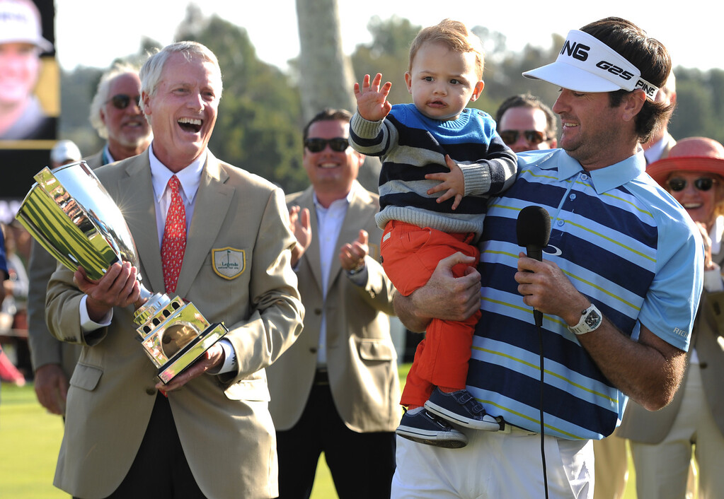 . Frederick H. Waddell, the Chief Executive Officer of Northern Trust Corporation, enjoys seeing Bubba Watson hold his son Caleb moments after the little boy ran out into the middle of the trophy presentation to be with his father. Watson won the 2014 Northern Trust Open with a score of 15 under par. Pacific Palisades, CA. February 16, 2014 (Photo by John McCoy / Los Angeles Daily News)