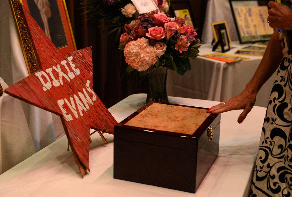 . Kitten DeVille touches the wooden box urn holding Dixie Evans\' ashes after friends and family attended a memorial service for Evans Sunday, September 1, 2013, at Palm Mortuary in Las Vegas. Jennifer Cappuccio Maher/Inland Valley Daily Bulletin