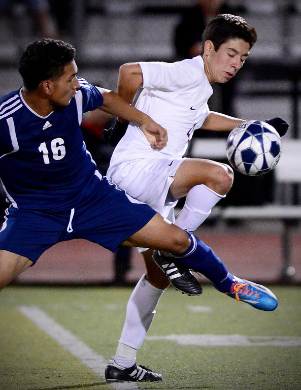 . Arcadia\'s Adam Alonzo (4) drives the ball as Anaheim\'s Elliot Carillo (16) approaches during the quarterfinals at Arcadia High School Thursday, February 27, 2014. Arcadia was defeated 2-0. (Photo by Sarah Reingewirtz/Pasadena Star-News)