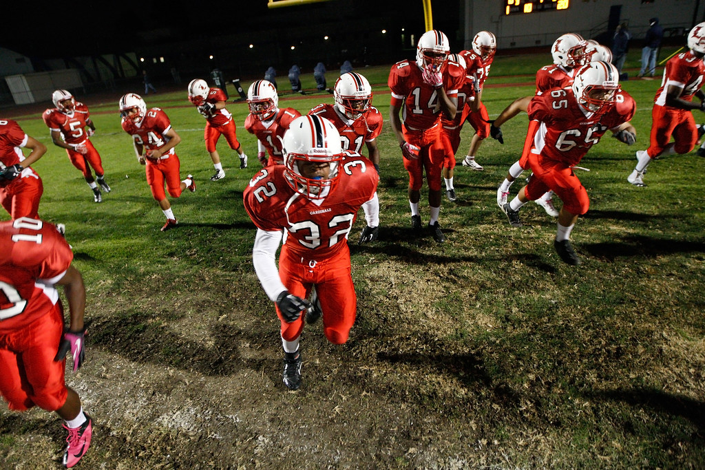 . Lawndale players run onto the field before kickoff against El Segundo in a Pioneer League matchup at Leuzinger High School on Friday, October 11, 2013 in Lawndale, Calif.  (Michael Yanow / For the Daily Breeze)