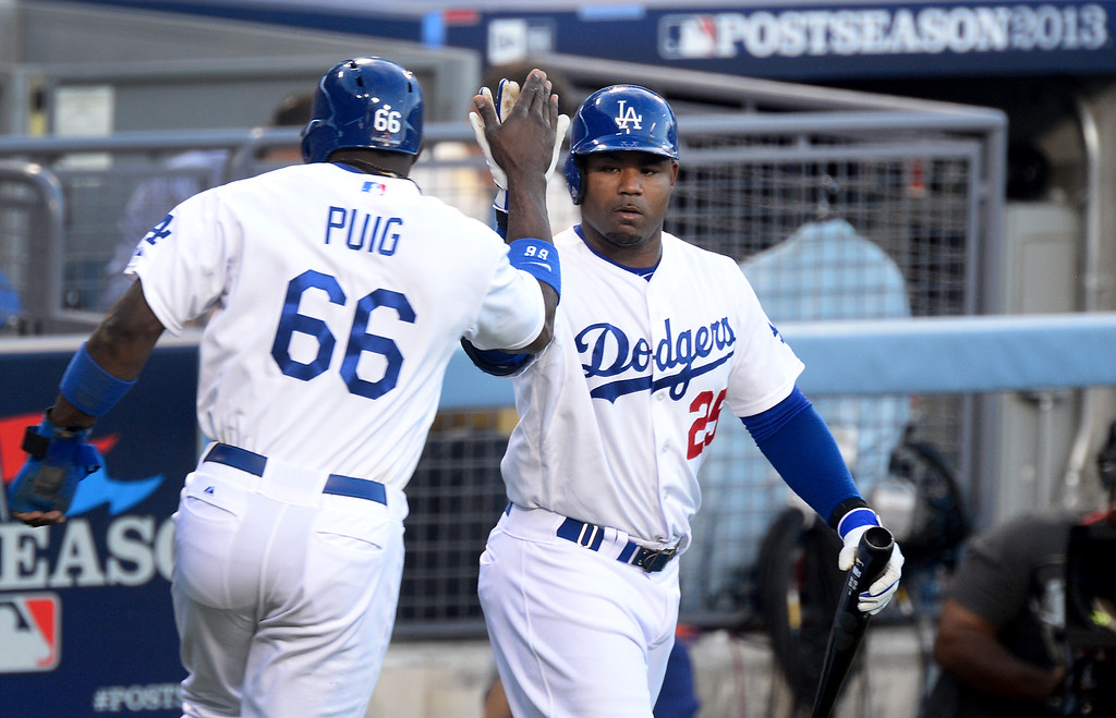 . Los Angeles Dodgers\' Carl Crawford, right, celebrates the first run in of game 3 in the second inning with Yasiel Puig as they play the Atlanta Braves during game 3 of the NLDS at Dodger Stadium Sunday, October 6, 2013. (Photo by Sarah Reingewirtz/Los Angeles Daily News)