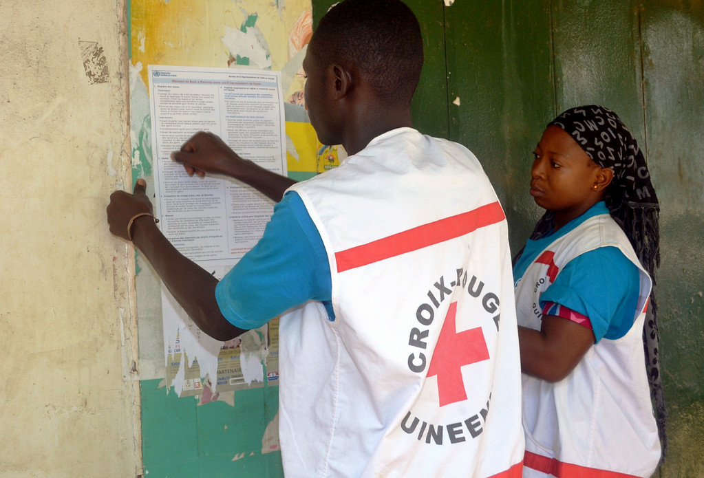 . Members of the Guinean Red Cross stick information concerning the Ebola virus during an awareness campaign on April 11, 2014 in Conakry. Guinea has been hit by the most severe strain of the virus, known as Zaire Ebola, which has had a fatality rate of up to 90 percent in past outbreaks, and for which there is no vaccine, cure or even specific treatment. The World Health Organization (WHO) has described west Africa\'s first outbreak among humans as one of the most challenging since the virus emerged in 1976 in what is now the Democratic Republic of Congo.         (CELLOU BINANI/AFP/Getty Images)