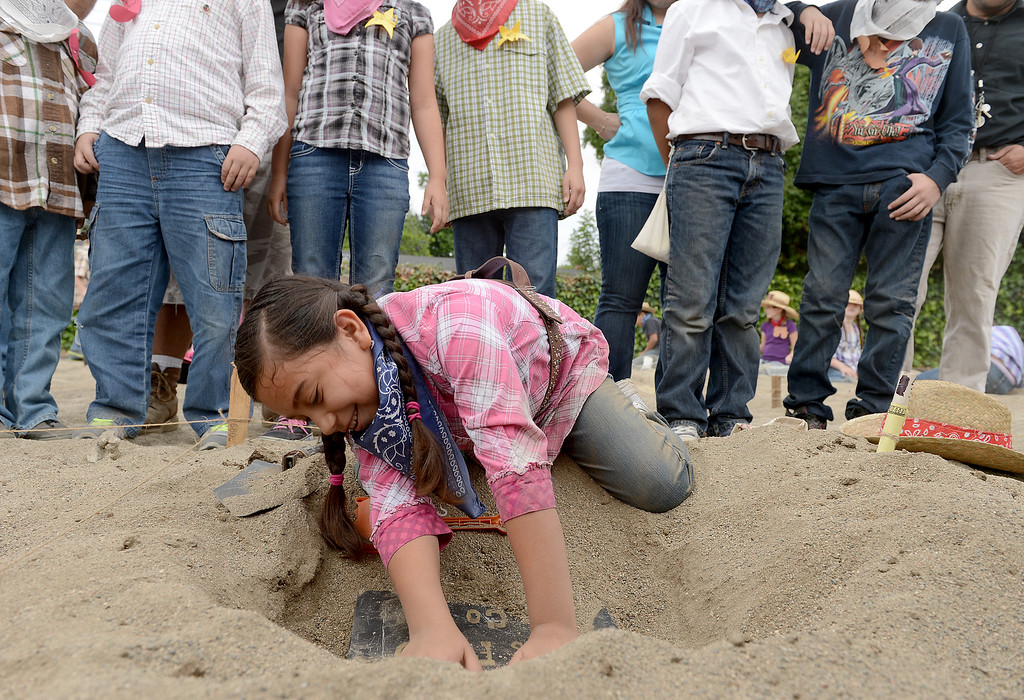 . Jazzlyn Gonzalez, 9, digs out a Wells Fargo strong box at the annual Gold Rush Day at Sierra Vista Elementary School in Upland May 17, 2013. About 60 students paned for gold while learned all about the Gold Rush at the school.  (Thomas R. Cordova/Staff Photographer)