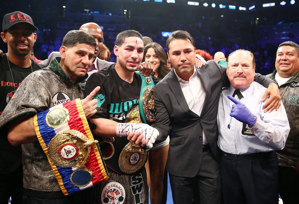 . NEW YORK, NY - APRIL 27:  Danny Garcia poses with the referee and promoter Oscar De La Hoya after defeated Zab Judah during the WBA Super and WBC Super Lightweight title fight at Barclays Center on April 27, 2013 in the Brooklyn borough of New York City.  (Photo by Elsa/Getty Images)