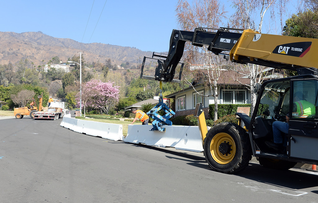 . Glendora public works crews place concrete barriers to divert possible water and flood flows on Brown Sage Drive Tuesday February 25, 2014. Possible heavy rains in the coming days could create mud flows off of the burned hill sides caused by January\'s Colby Fire. (Will Lester/Inland Valley Daily Bulletin)