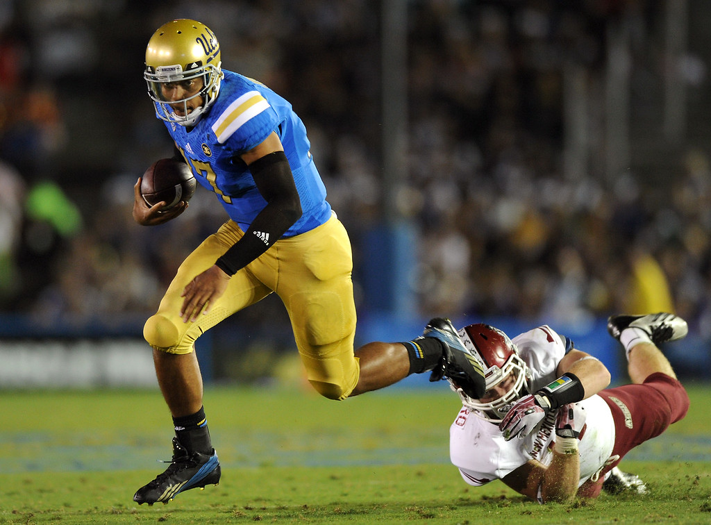 . UCLA QB Brett Hundley scrambles away from New Mexico State LB Clint Barnard in the second quarter, Saturday, September 21, 2013, at the Rose Bowl. (Photo by Michael Owen Baker/L.A. Daily News)