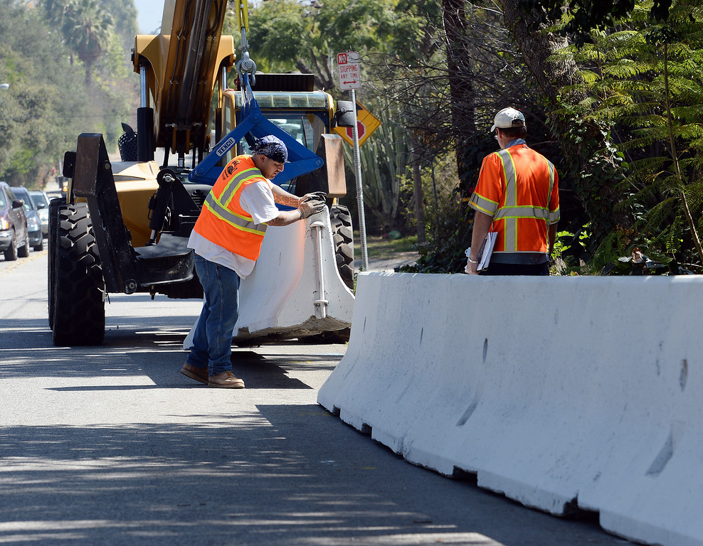 . Glendora public works crews place concrete barriers to divert possible water and flood flows on Sierra Madre Avenue Tuesday February 25, 2014. Possible heavy rains in the coming days could create mud flows off of the burned hill sides caused by January\'s Colby Fire. (Will Lester/Inland Valley Daily Bulletin)