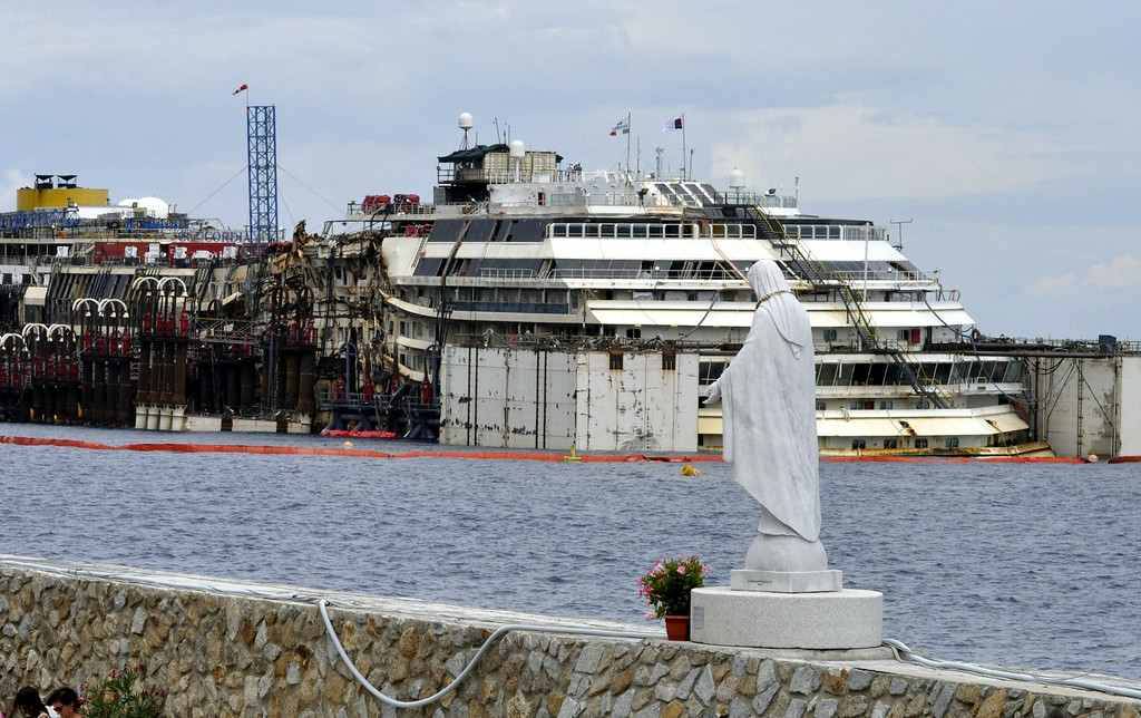 . A statue of the Madonna stands at the port of the Tuscan island of Giglio, Italy, as operations to refloat and tow away the luxury cruise ship Costa Concordia get underway, Monday, July 14, 2014. The heavily listing ship was dragged upright in a daring maneuver last September, and then crews fastened huge tanks to its flanks to float it. Towing is set to begin July 21. It\'s about 200 nautical miles (320 kilometers) to Genoa\'s port and the trip is expected to take five days. 30 months ago it struck a reef and capsized, killing 32 people. (AP Photo/Giacomo Aprili)