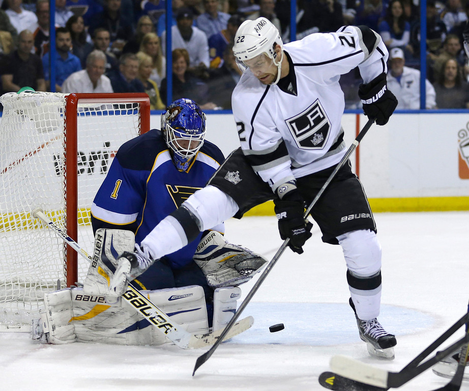 . St. Louis Blues goalie Brian Elliott, left, watches the puck as it goes between the legs of Los Angeles Kings\' Trevor Lewis during the first period in Game 5 of a first-round NHL hockey Stanley Cup playoff series, Wednesday, May 8, 2013, in St. Louis. (AP Photo/Jeff Roberson)
