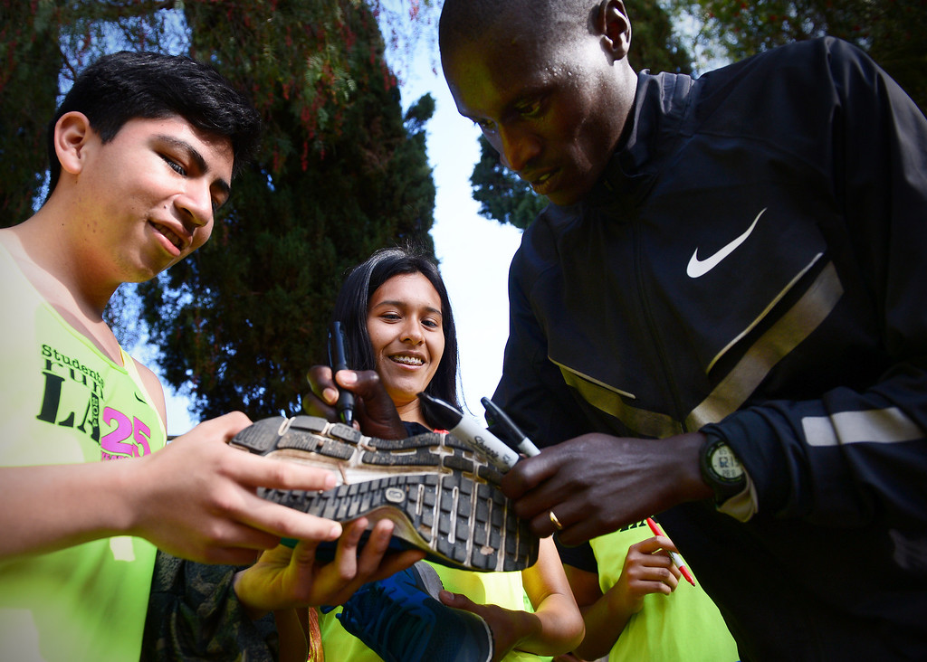 . Elite marathon runner Lani Rutto, of Kenya, signs shoes and jerseys as elite marathon athletes visit with students of Students Run LA program during a training run for the LA Marathon at Griffith Park in Los Angeles Friday, March 7, 2014. The students will also be running Sunday\'s marathon. (Photo by Sarah Reingewirtz/Pasadena Star-News)