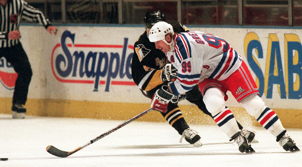 . New York Rangers center Wayne Gretzky (99) chases the puck in the first period against the Pittsburgh Penguins Monday, March 24, 1997, in New York. (AP Photo/Kevin Larkin)