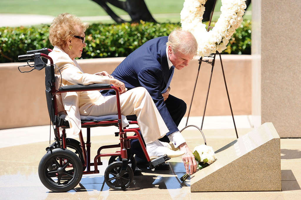 . Fred Ryan (Chairman of the Board of Trustees for the Ronald Reagan Presidential Foundation) helps Nancy Reagan place roses at the grave site of her husband, Ronald Reagan, at the Ronald Reagan Presidential Library and Museum June 5, 2014 in Simi Valley. (Andy Holzman/Los Angeles Daily News)