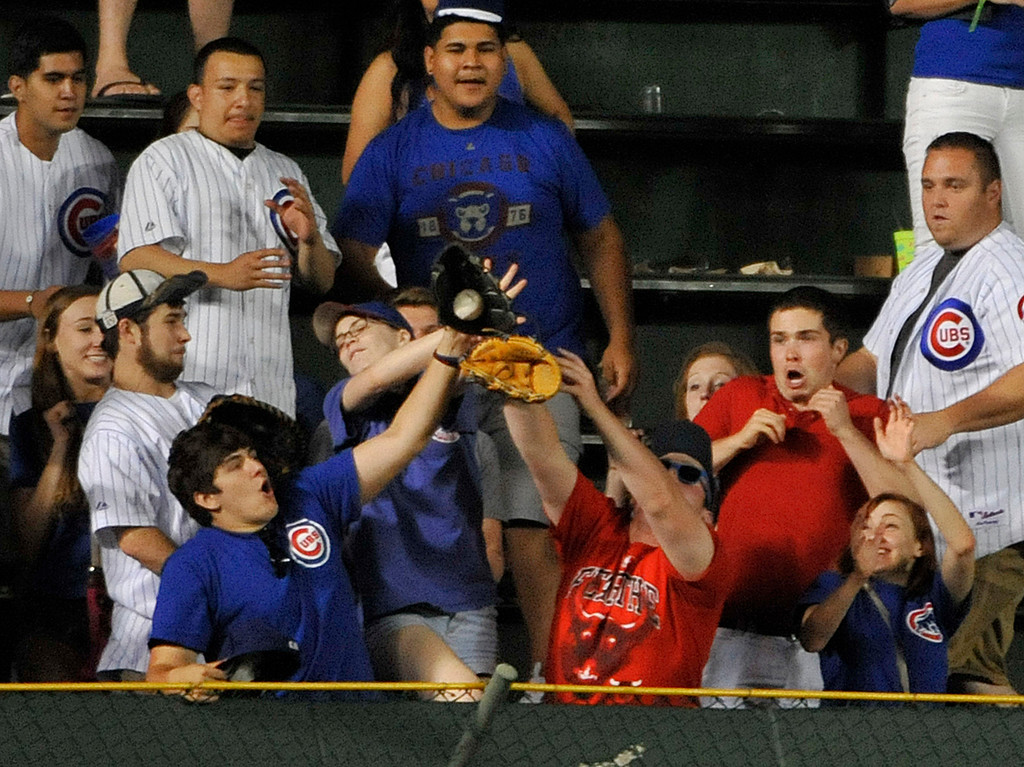 . CHICAGO, IL - JULY 10: Fans try and catch a home run off the bat of Cody Ransom #1 of the Chicago Cubs during the ninth inning against the Los Angeles Angels of Anaheim on July 10, 2013 at Wrigley Field in Chicago, Illinois. The Los Angeles Angels of Anaheim defeated the Chicago Cubs 13-2. (Photo by David Banks/Getty Images)