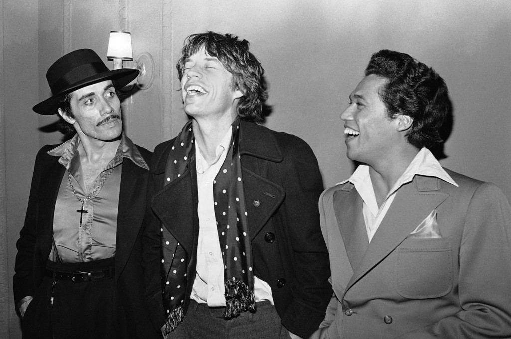 . Actor Edward James Olmos, left, star of the new Broadway musical �Zoot Suit�, watches rock personality Mick Jagger chuckle, March 23, 1979 after performance in New York.  Man at right is unidentified. (AP Photo/Richard Drew)