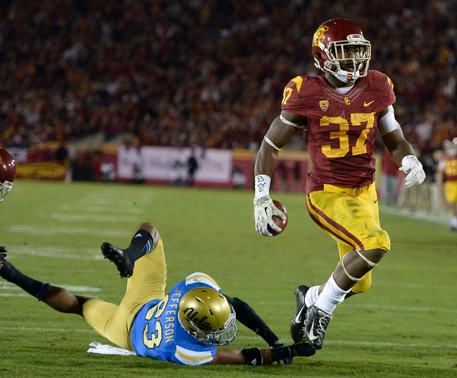 . USC Javorius Allen gets past UCLA Tre Madden in the 2nd quarter. UCLA and USC played in a matchup of cross town rivals at the Los Angeles Memorial Coliseum in Los Angeles, CA.  photo by (John McCoy/Los Angeles Daily News)