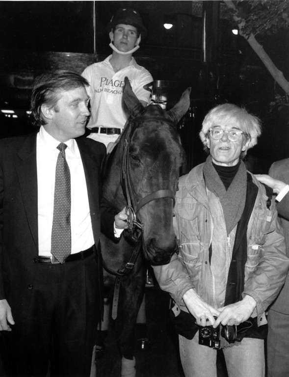 . Donald Trump owner of New York\'s Trump Tower, holds the bridle of a polo pony while talking to Andy Warhol on Nov. 4, 1983.  Yale University polo player Eric Stever sits astride the horse.  (AP Photo/Mario Suriani)