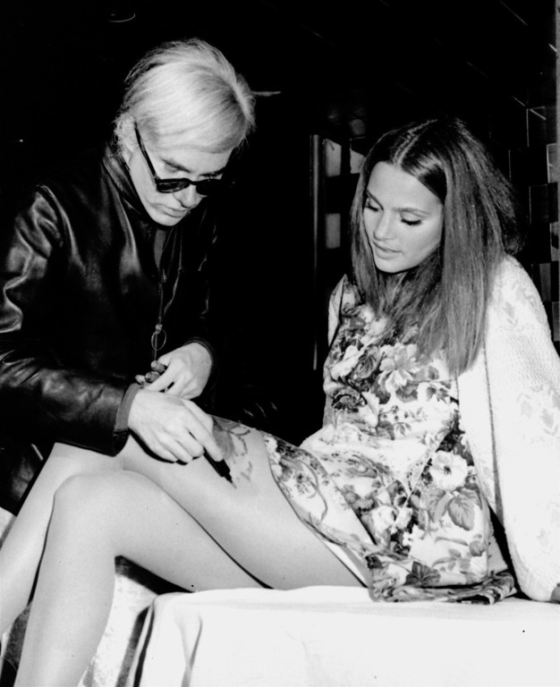 ". Popularizing a new style, artist Andy Warhol paints decorations on the thigh of Leigh Taylor-Young, starring in ""I Love You, Alice B. Toklas,\"" at L\'Etoile Restaurant in New York, Oct. 1, 1968.  Miss Taylor-Young wears a painted butterfly on her thigh in the new comedy, and thus became the first screen star to wear the new fashion in a film.  (AP Photo)"