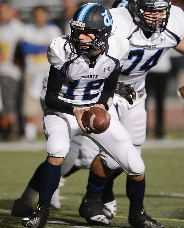 . Duarte quarterback Isaiah Scott (12) hands-off against Bassett in the first half of a prep football game at Bassett High School in La Puente, Calif., on Friday, Nov. 1, 2013.    (Keith Birmingham Pasadena Star-News)