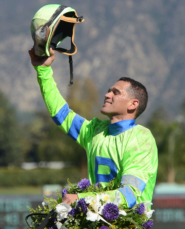 ". Jockey Javier Castellano atop ""Ria Antonia\"" holds his helmet high after winning the fourth race during the Breeders\' Cup at Santa Anita Park in Arcadia, Calif., on Saturday, Nov. 2, 2013.    (Keith Birmingham Pasadena Star-News)"
