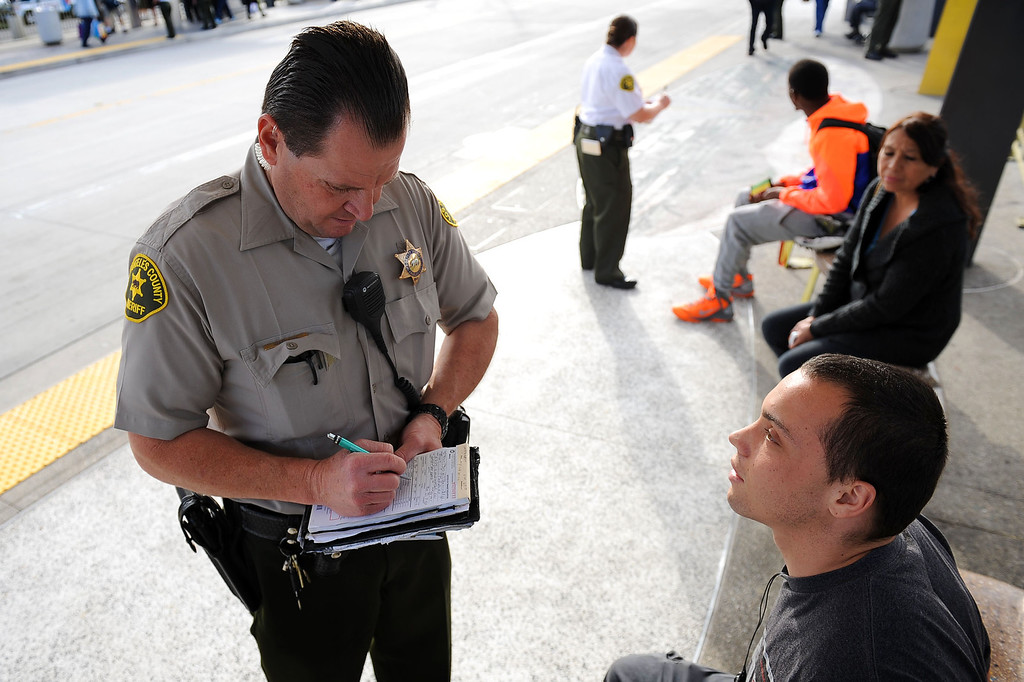 . LA County Sheriff deputy Ken Cianciosi cites a bus rider for fare evasion during an Orange Line fare enforcement operation at the Van Nuys Orange Line Station February 25, 2014.  Officials from Metro and the Los Angeles Sheriff\'s Department Transit Services Bureau announced a new two-pronged effort to cut down on fare-evaders on the Orange Line by improving communications and beefing up enforcement.(Andy Holzman/Los Angeles Daily News)