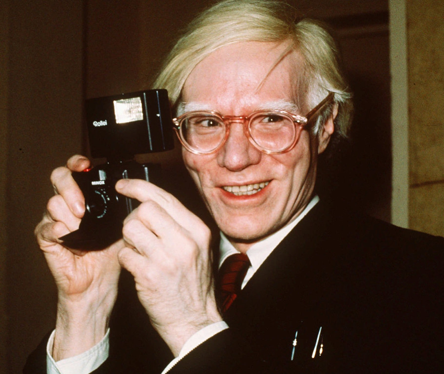 . Pop artist Andy Warhol smiles in New York in this 1976 file photo. Taking a cue from the artist himself, the Andy Warhol Museum collected stuff to seal into a ``time capsule\'\' of 1997 during a New Year\'s Eve cocktail party.  ``I stole the idea from Andy,\'\' said Andy Newman, the editor of City Paper, a news and entertainment weekly in Pittsburgh. ``We were looking for a way of doing the `Year in Review\' issue less predictably.\'\'  Warhol began compiling time capsules in 1974 when he moved to a new studio in New York. (AP Photo/Richard Drew,File)
