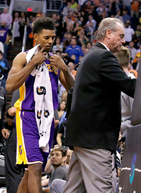 . Los Angeles Lakers\' Nick Young, left, is escorted from the court by security after being ejected following a scuffle with the Phoenix Suns during the first half of an NBA basketball game Wednesday, Jan. 15, 2014, in Phoenix. Suns\' Alex Len was ejected from the game for a flagrant foul. (AP Photo/Ross D. Franklin)