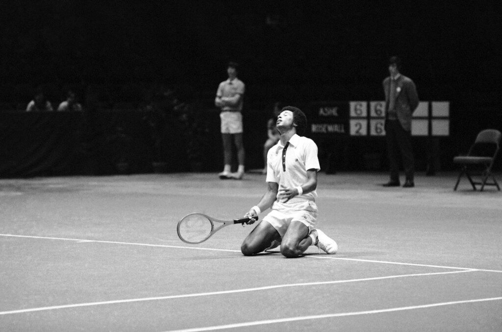 . Arthur Ashe of the United States drops to his knees after missing a tie-breaking point in second set of his match with Ken Rosewall of Australia in United States Professional Indoor Tennis Championships in Philadelphia on Saturday, Feb. 12, 1972. Rosewall defeated Ashe in this semi-final round, 2-6, 7-6, 7-6, 6-2. (AP Photo/Bill Ingraham)