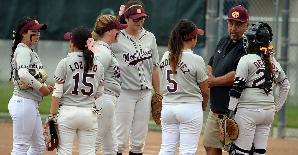 . West Covina head coach Jesse Mendez talks to his team in the fourth inning of a prep softball game against Bonita at Los Flores Park in La Verne, Calif., on Thursday, March 27, 2014. Bonita won 6-3. (Keith Birmingham Pasadena Star-News)